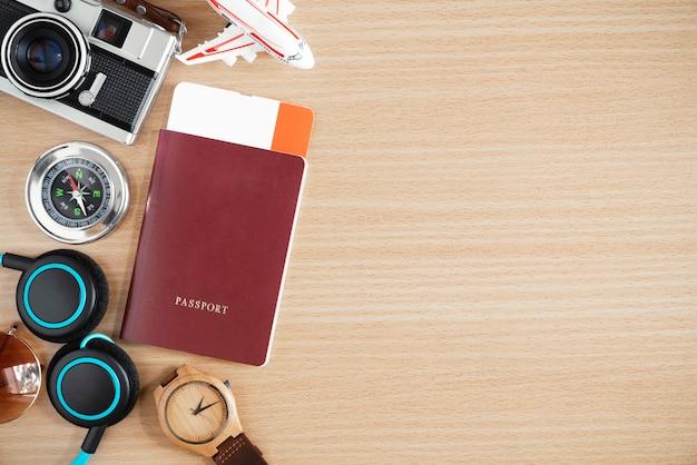 旅行のコンセプト背景。パスポート、コンパス、アクセサリー、木製テーブルにテキストのための自由なスペース。