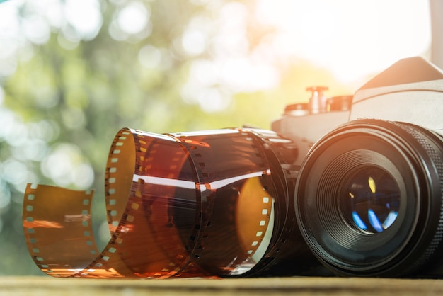 地面にフィルムロールとヴィンテージカメラ。旅行の背景