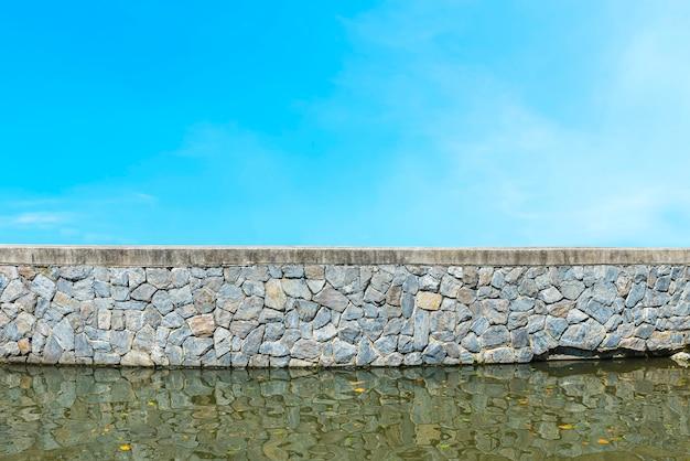 水と青空の古い石の壁。