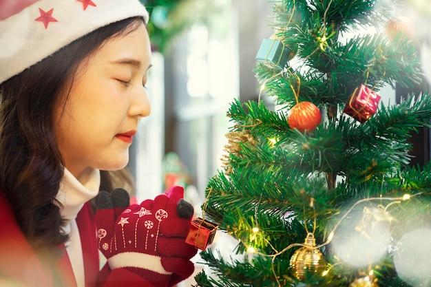 Красивая женщина в красной одежде молится в канун рождества с елкой и аксессуарами