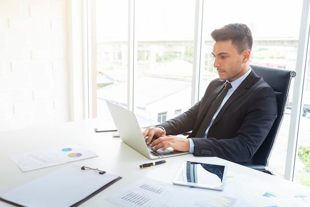 オフィスでラップトップと紙のグラフと机で働く、丁寧なビジネスマン。