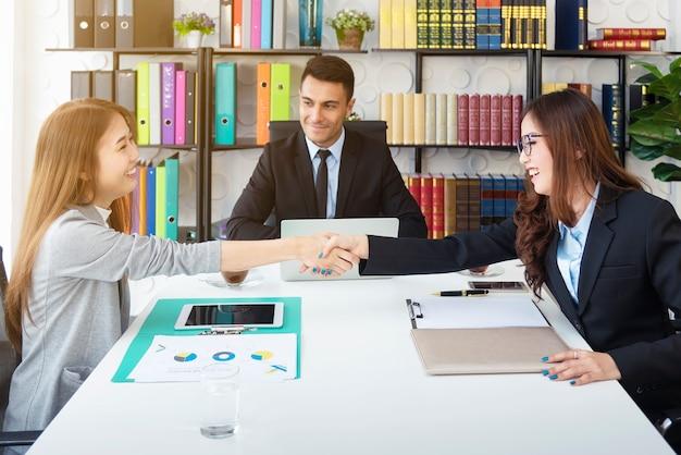 成功ビジネスコンセプト。オフィスでたくさん取引を終えた後幸せとビジネス人々ハンドシェイク