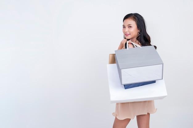 白い背景の上に笑みを浮かべて買い物袋を保持しているかなり若い女性。