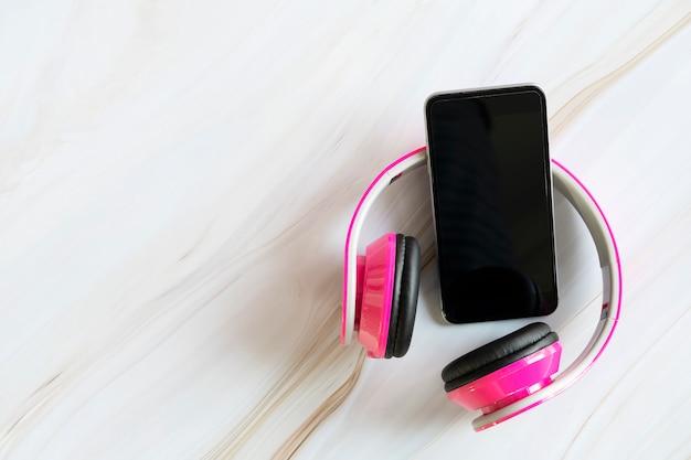 テキストの無料コピースペースを持つ白い大理石のテーブルの上の携帯電話とピンクのヘッドフォン。