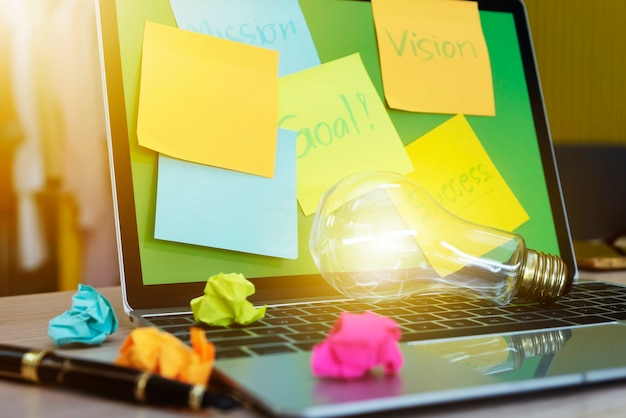 アイデアと創造的な概念ラップトップ上の電球のクローズアップ。