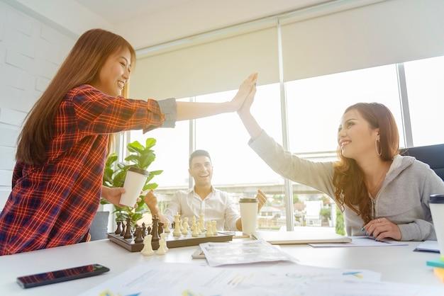 成功のビジネスコンセプトです。近代的なオフィスに一緒に祝っているビジネス人々。