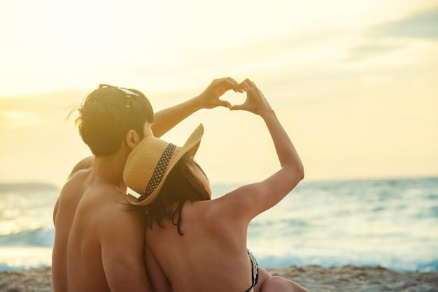 ロマンスカップルは夕暮れ時のビーチで手で一緒にハート形をしました。