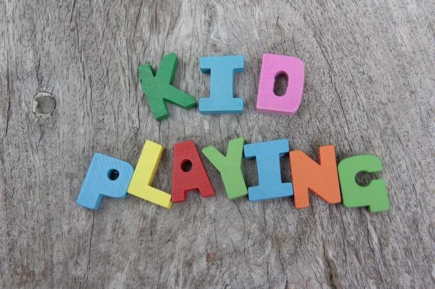 木製の床で遊ぶ言葉の子供とカラフルな木製のアルファベットのブロック