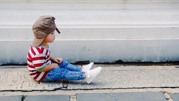 Мальчик утомленного ребенк азиатский сидя на поле с пакостной бетонной стеной