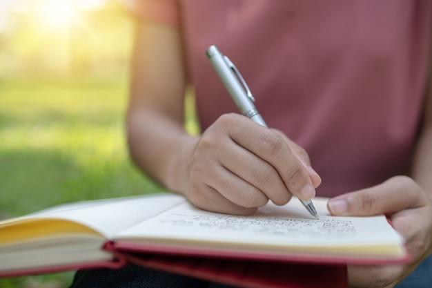 公園でノートに書いて座っているを閉じる