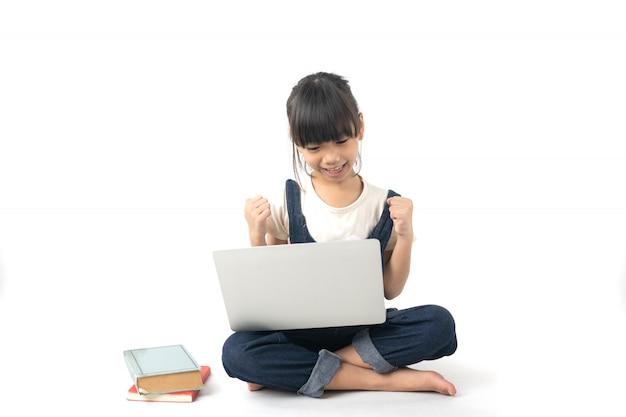 Молодая азиатская радостная и счастливая девушка студента смотря на компьтер-книжке изолированной на белой предпосылке