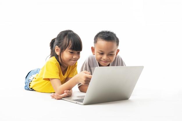 若いアジアのタイの子供たち、男の子と女の子の敷設と技術とマルチメディアによって学ぶためにラップトップを探して