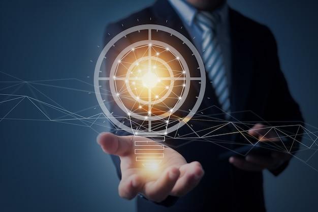 革新と技術の概念、ビジネスマン持株通信電球とインターネットネットワークディスプレイを接続する創造的な電球を保持
