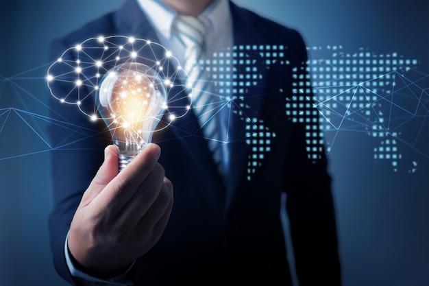 Концепция инноваций и технологий, бизнесмен держит в руках креативную лампочку с линией соединения для связи с дисплеем в сети интернет, инновации и развитие неограниченного числа людей