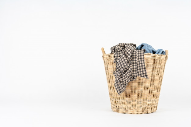 Плетеная корзина с одеждой на белом фоне
