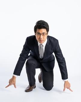 スーツのアジア系のビジネスマンを実行する準備