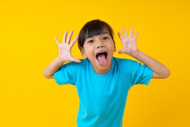 アジアの若い女の子の表情とうれしそうな、タイの子供の肖像画は楽しさと黄色の無邪気さを持っています。