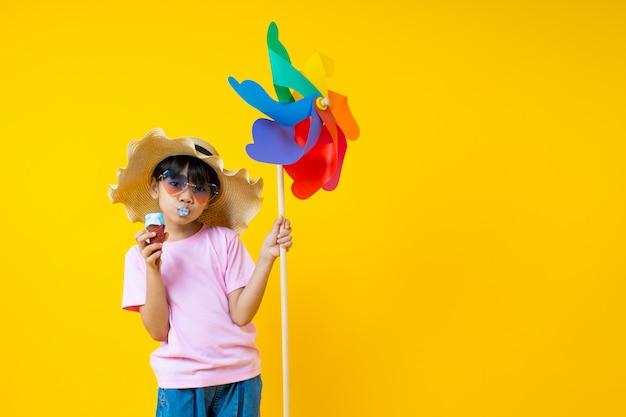 カラフルなタービンを押しながら黄色のアイスクリームを食べる若いアジア美少女の肖像画