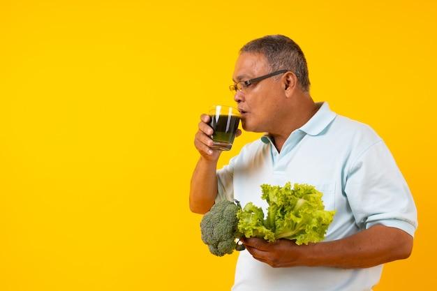 アジアの老人が野菜ジュースを飲んで、タイの高齢者は健康ドリンクのガラスを飲むとサラダを保持