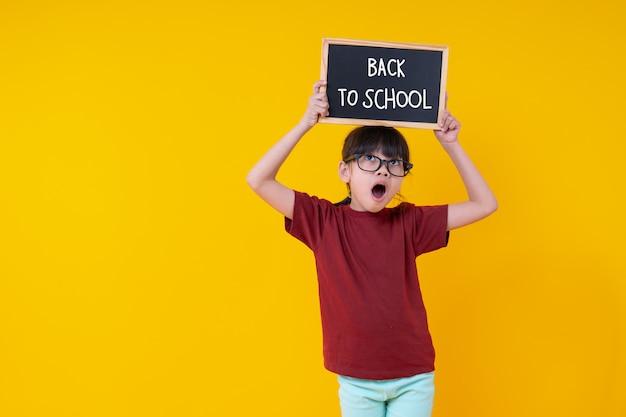学校の言葉に戻って頭の上に小さな黒板を保持している若いアジアのタイの女子学生、すごい、驚いた子供