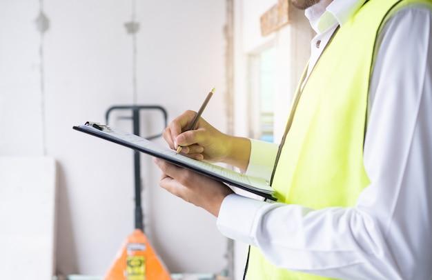 検査官またはエンジニアが建設現場で請負業者の作業をチェックしています