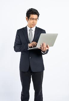 フォーマルなスーツのビジネスマンは分離されたラップトップを使用します