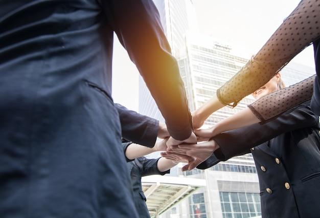 参加力と成功したチームのコンセプト、一緒に手を結ぶビジネスマン