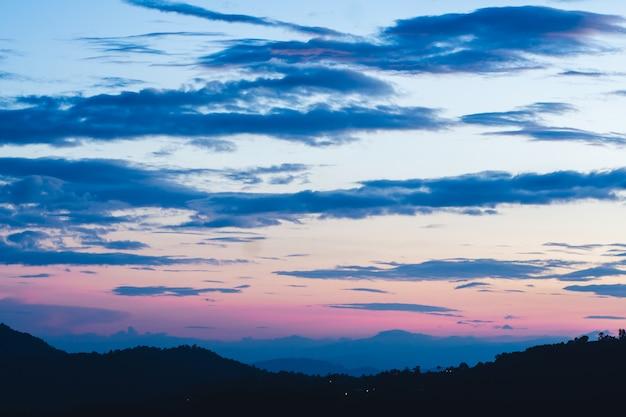 空と暗い木と山に沈む夕日