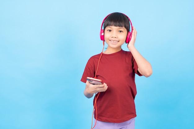 Тайская азиатская девушка малыш слушает музыку, носить розовые наушники