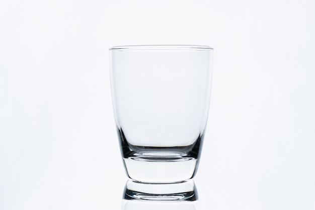 白い壁に分離された水の空のグラス
