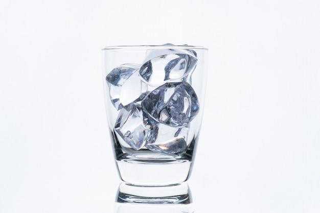 白い壁に分離されたアイスキューブとガラス