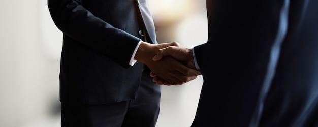 成功したコミュニケーション、交渉、経済的成功、および起業、最高のマーケティング、目標達成への企業祝賀の後に、パートナーとのプロの若手ビジネスハンドシェイク