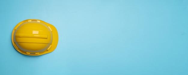 水色の壁に黄色の建設と保護ヘルメット