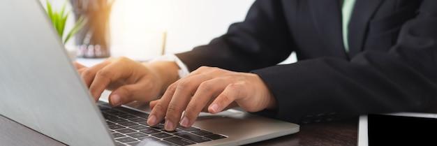 Закройте вверх по коммерсантке в сюите используя портативный компьютер. женщина работает на ноутбуке на рабочем столе
