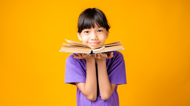 本を持っている若いアジアの女の子の肖像画、紫のシャツを着たタイの学生の子供の笑顔