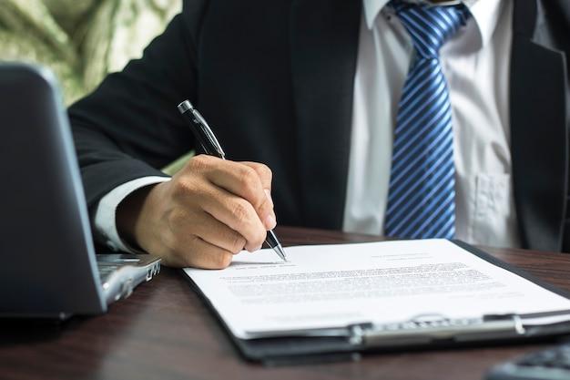 Бизнесмен или адвокат, подписывающий контрактную бумагу