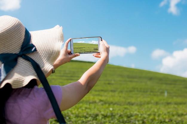 旅行者の女性が電話を持っていて、緑の風景を撮った写真を撮る