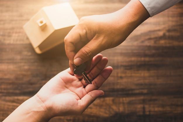 不動産の概念、家の代理店の銀行家は木製のテーブルの所有者またはバイヤーに家の鍵を与える