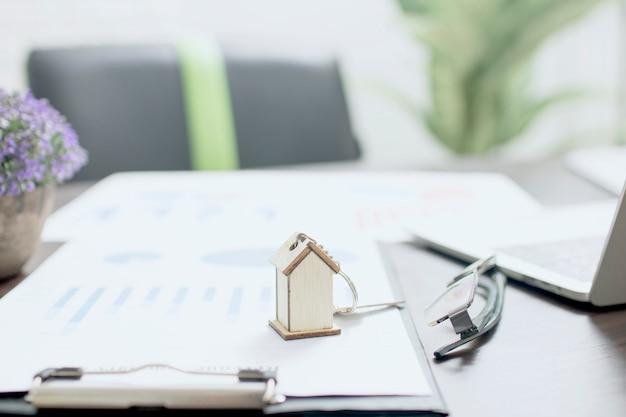 Концепция недвижимости, модель дома на финансовой бумаге с ключом дома на столе