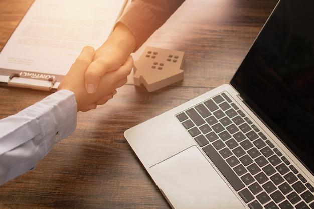 不動産の概念、銀行家代理店は成功したコミュニケーションの後にクライアントまたは家の購入者と握手し、契約に署名します