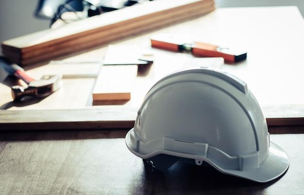 作業デスク上の安全ヘルメットとテーブル上の大工用具に焦点を当てる