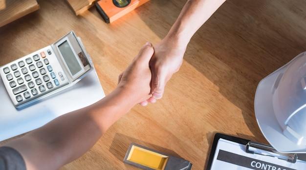 作業テーブル上で手を振るアーキテクチャとエンジニアのトップビュー