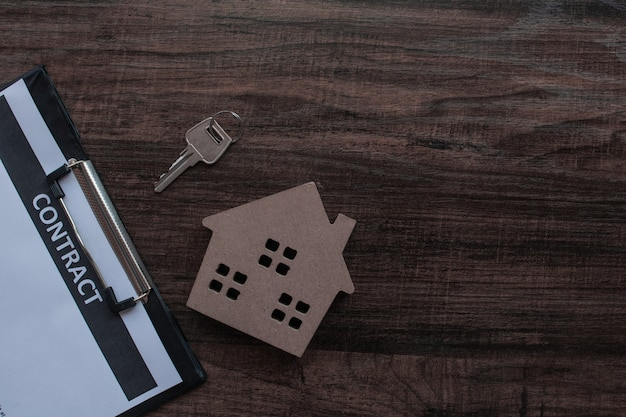 木製のテーブルの上の家の鍵を持つ不動産と契約紙