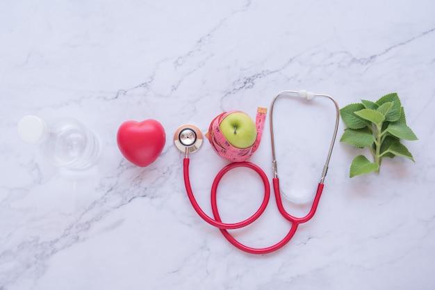 健康的な概念、赤いハートと白い大理石の背景に聴診器と青リンゴとピンクのダンベルの平干し