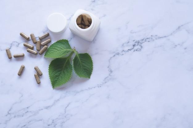 Фитотерапия в капсулах на деревянной ложке с натуральным зеленым листом на белом мраморе