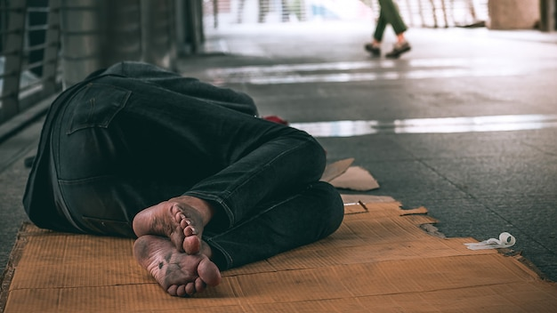 市内の都市通りの汚れた床で寝ているホームレスの男性の足を閉じる