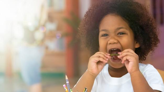 Маленький ребенок дети, улыбаясь, едят закуски от счастья.