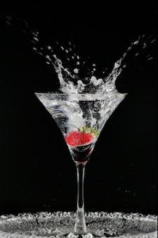 Коктейль с клубникой, изолированных на черном фоне. стакан водки брызгает.