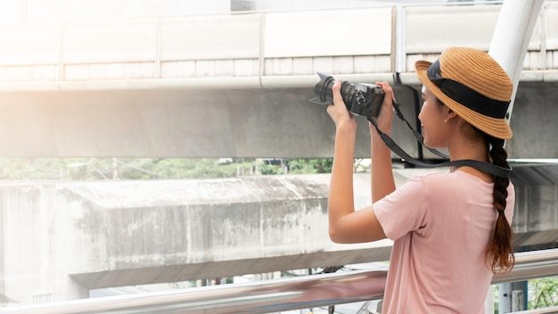 カメラ旅行写真が付いている都市で幸せなかなり若いアジア女性の肖像画。