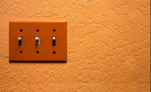 レトロなオレンジ色の壁にヴィンテージの電気スイッチ